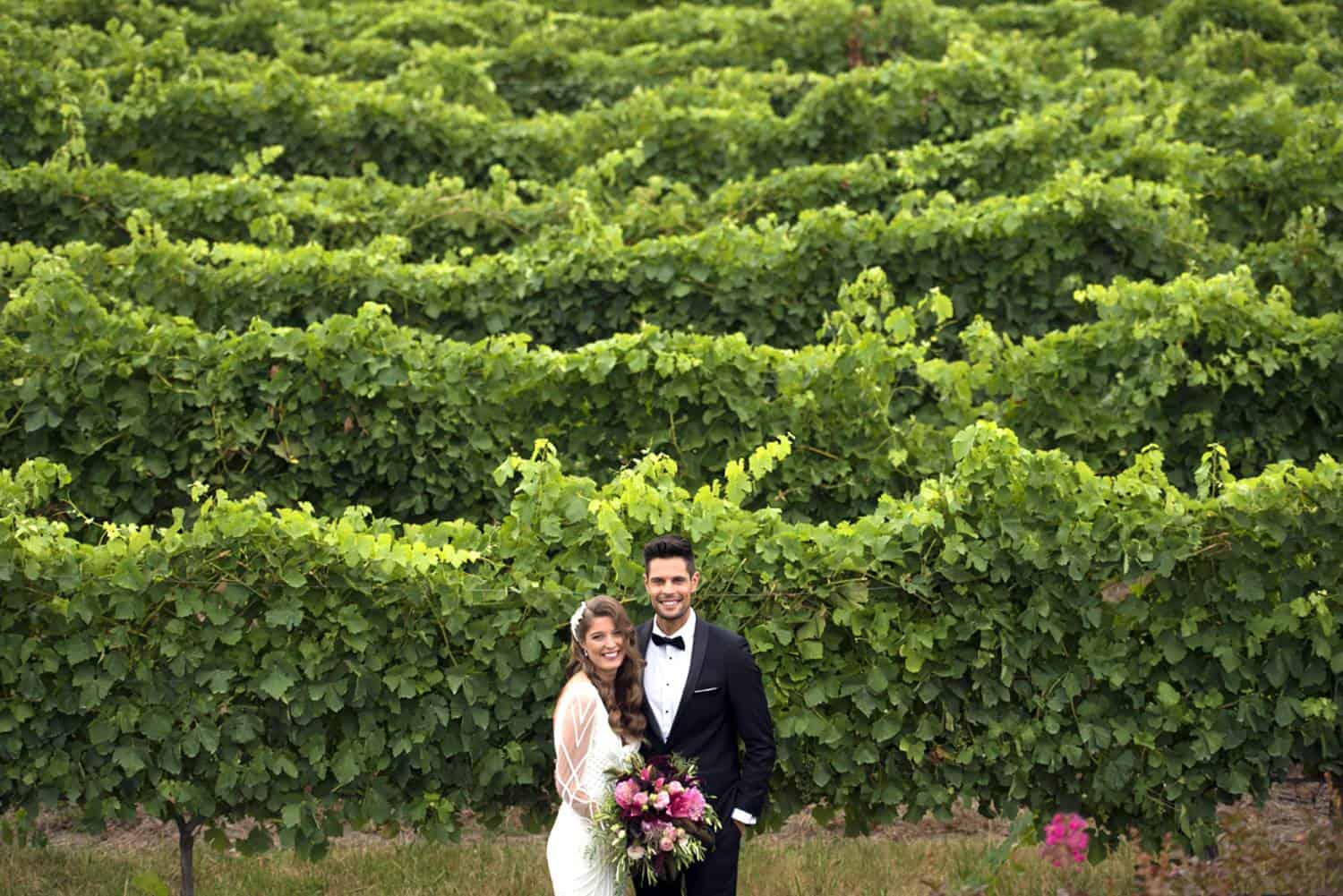 wedding couple stand in front of vineyard at yarra valley
